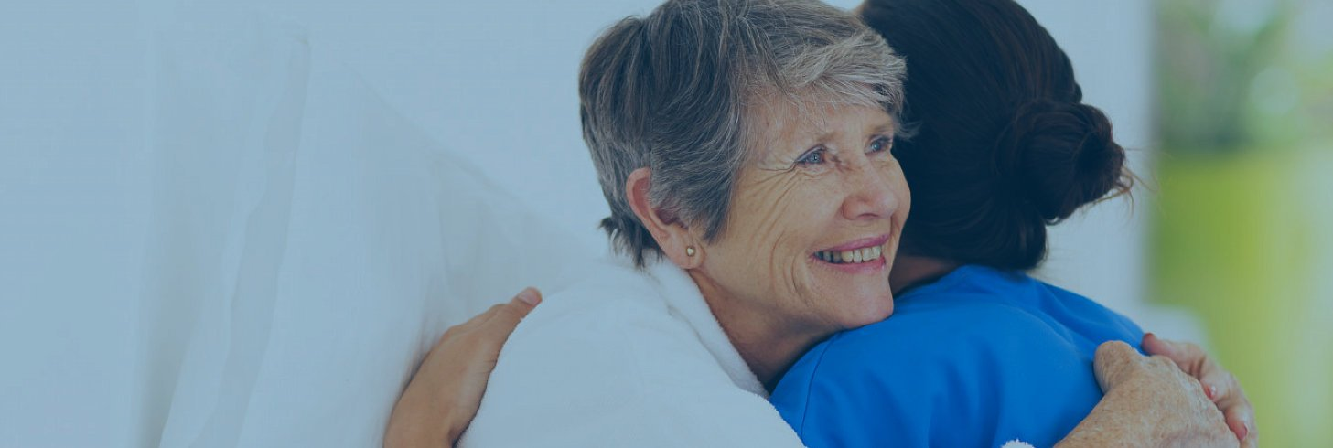 Caregiver and elderly woman hugging each other